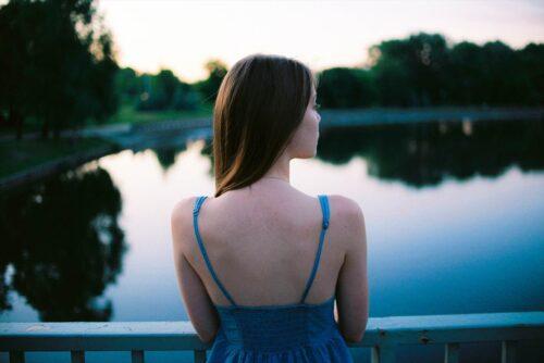 池のほとりに佇む後ろ姿の女性
