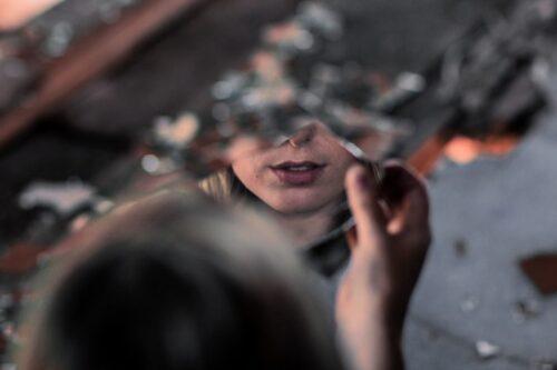 割れた鏡で顔を見る女性