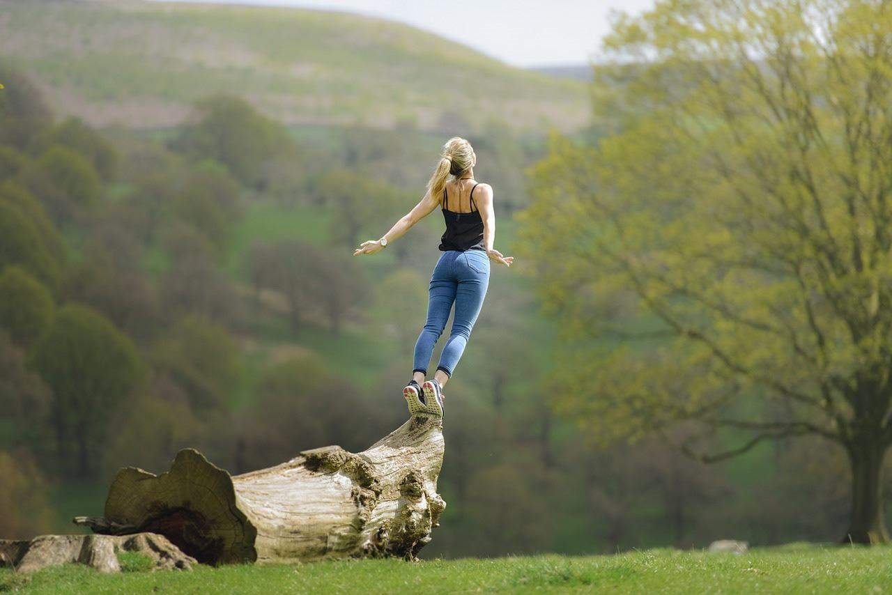 倒木から今にもジャンプしようという女性