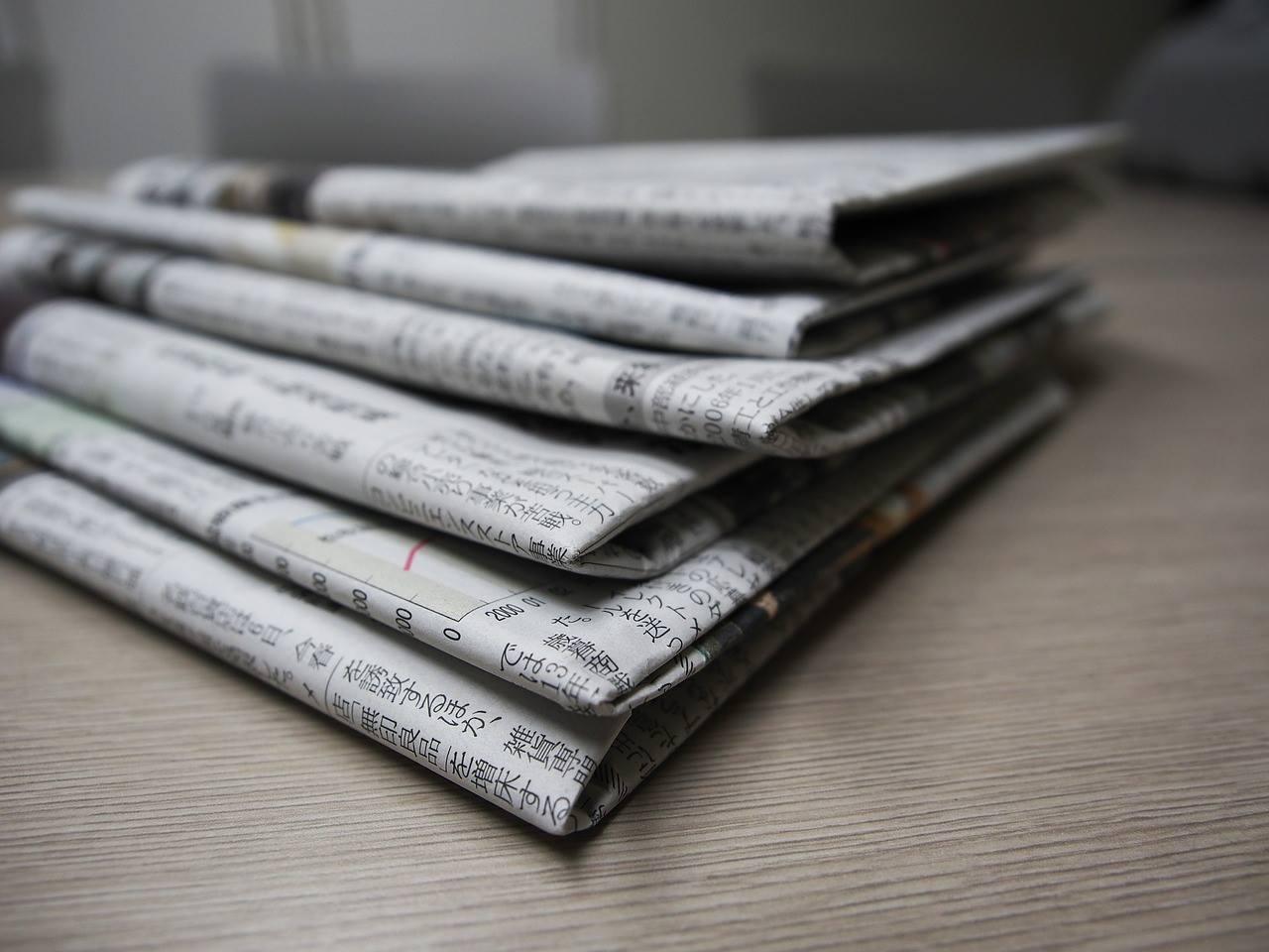 新聞朝刊を何部か重ねた写真