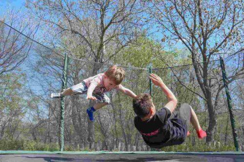 屋外のトランポリンで遊ぶ子どもたち