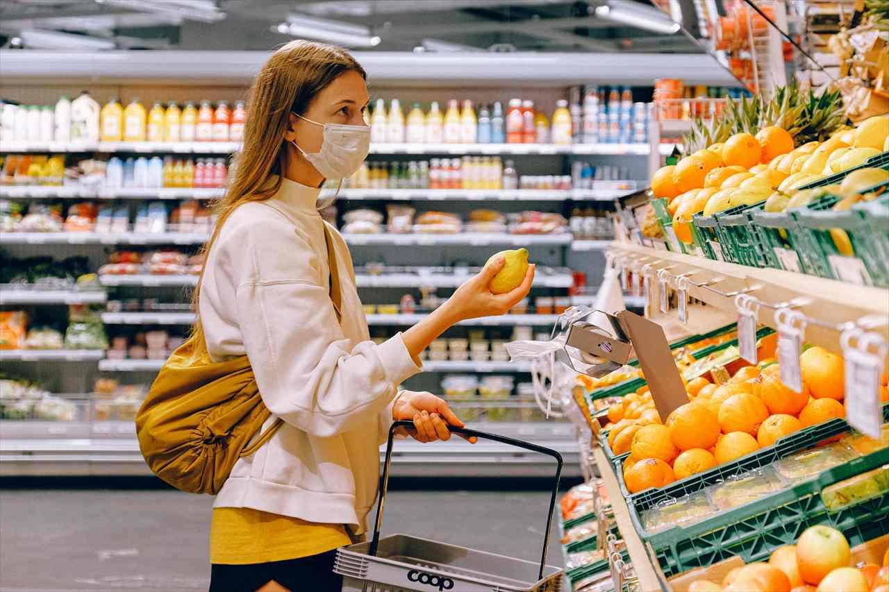 スーパーでレモンを選ぶ女性