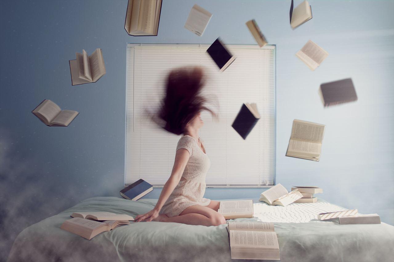 女性のまわりを本が飛び回っている